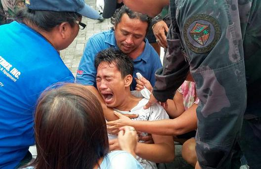 A survivor of a passenger ferry that capsized in rough waters cries after arriving at the pier in Ormoc City, central Philippines on July 2. At least 36 people were killed after a passenger ferry with close to 200 people on board capsized in rough waters in the central Philippines