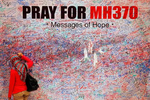 woman leaves messages of support and hope for passengers of missing Malaysia Airlines MH370 in central Kuala Lumpur...A woman leaves a messages of support and hope for the passengers of the missing Malaysia Airlines MH370 in central Kuala Lumpur.