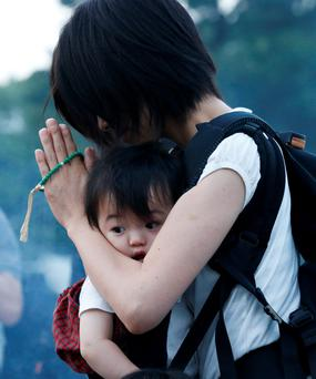 A woman carrying her baby, prays for the atomic bomb victims in front of the cenotaph for the victims of the 1945 atomic bombing, at Peace Memorial Park in Hiroshima.