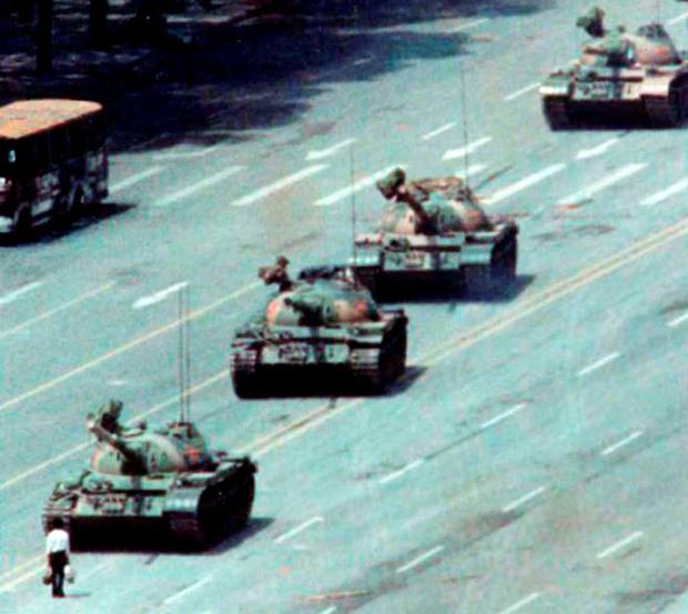 Tank Man stands in front of a column of tanks in Beijing