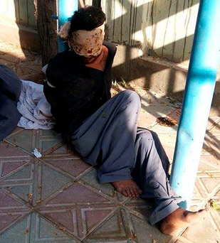 An arrested Taliban fighter lies in a courtyard of Kunduz as Afghan forces and NATO allies claim to have wrestled back control of the city