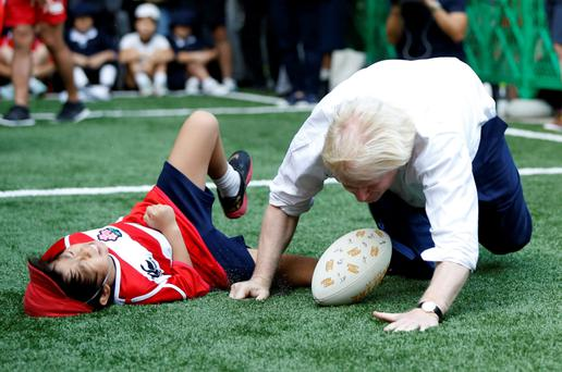 London's Mayor Boris Johnson collides with 10-year-old Toki Sekiguchi during a game of street rugby with a group of Tokyo children, outside the Tokyo Square Gardens building yesterday