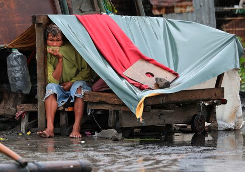A Filipino man sits inside his makeshift home as the typhoon hits the coastal town of Navotas, north of Manila