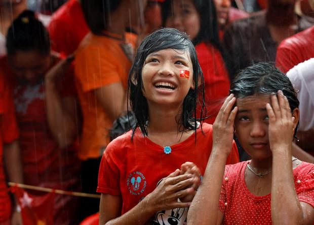 Young supporters celebrate in the rain as they wait for official results of the election in front of the National League for Democracy Party head office at Yangon
