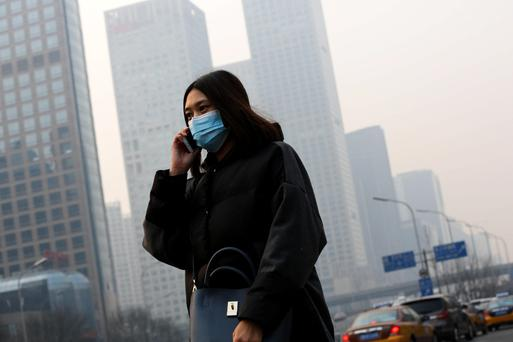 A woman wearing a mask to protect herself from pollutants walks past office buildings shrouded with pollution haze in Beijing.