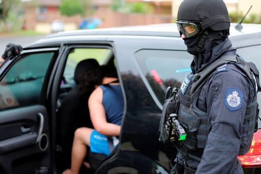 Heavily armed police officers detain a man during early morning raids in western Sydney, Australia