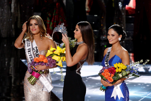 Miss Columbia has the crown taken from her head as Miss Philippines waits to be crowned Miss Universe in the farcical affair