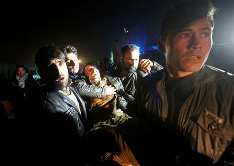 Afghan men carry a wounded man at the site of an explosion near Kabul airport in Afghanistan, yesterday. Photo: Reuters