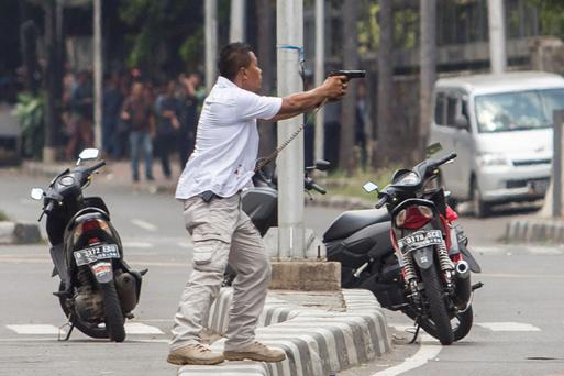 A plainclothes police officer aims his gun at attackers during a gun battle following explosions in Jakarta