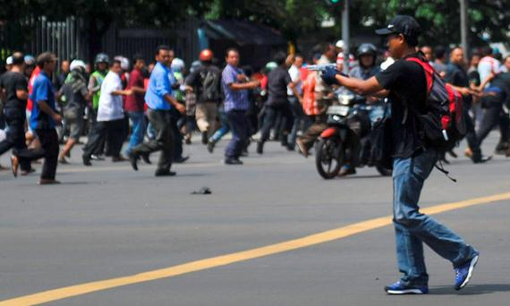 A man is seen holding a gun towards the crowd in central Jakarta, Indonesia when seven people were killed.
