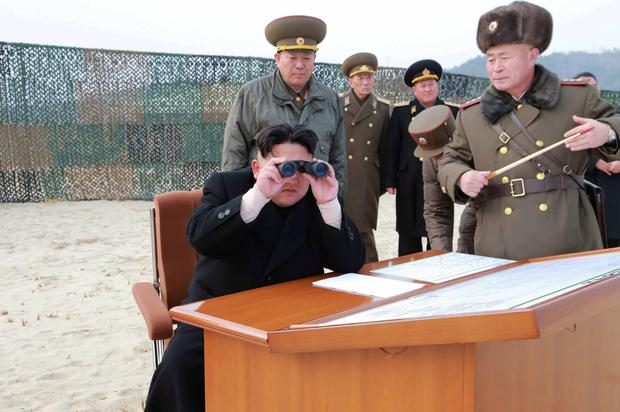 North Korean leader Kim Jong Un looks through a pair of binoculars as he guides the multiple-rocket launching drill.