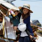 A woman carrying a young girl walks away from a collapsed house caused by an earthquake in Mashiki town, Kumamoto. Photo: Reuters