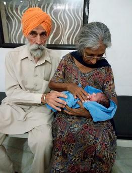 Indian couple Mohinder Singh Gill(L)poses with his wife Daljinder Kaur and their newly born baby at The National Fertility Centre in Hisar.