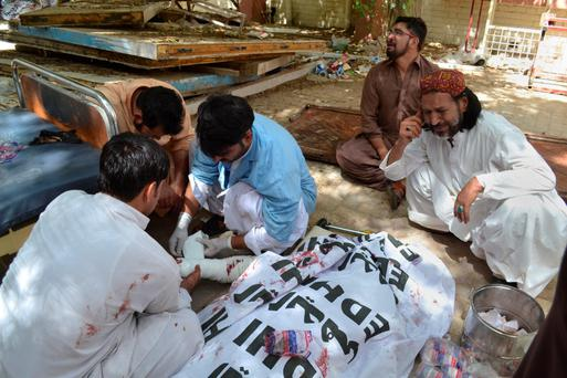 Men mourn a relative killed in a suicide bomb attack in the grounds of a hospital in Quetta, southwestern Pakistan Photo: AP