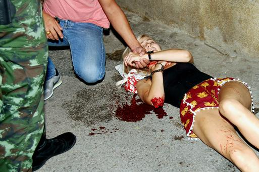 An injured woman receives first aid after two bombs exploded in the seaside resort of Hua Hin in Thailand. Photo: Reuters