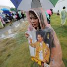 A woman carries a portrait of late Thai King Bhumibol Adulyadej outside the Grand Palace in Bangkok. REUTERS