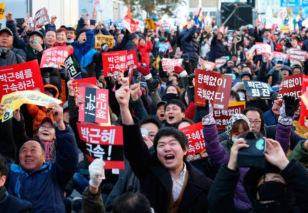 Protesters celebrate after hearing the news of President Park Geun-hye's impeachment in front of the National Assembly in Seoul, South Korea. (Photo: AP Photo/Ahn Young-joon)
