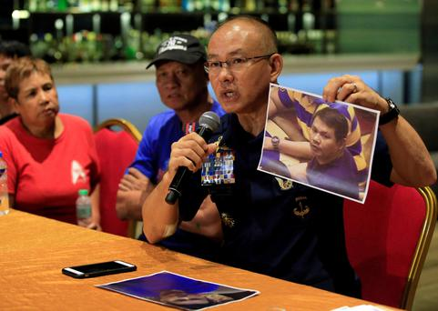 Police chief Oscar Albayalde holds up a picture of gunman Jessie Javier Carlos as the killer's devastated parents Fernando and Teodora sit beside him. Photo: Romeo Ranoco