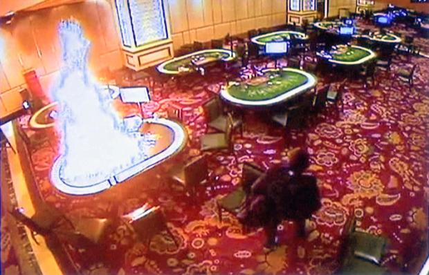 Gunman Jessie Carlos sets a gambling table on fire in the casino before walking away. Photo: AP