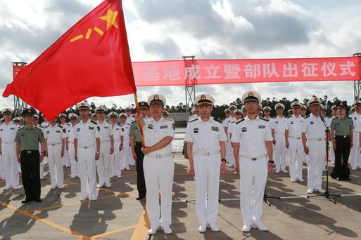 A soldier of China's People's Liberation Army holds a PLA flag as others stand guard at a military port in Zhanjiang, Guangdong province. Photo: Reuters