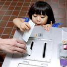 A girl casts her father's ballot at a polling station in Tokyo. Photo: REUTERS