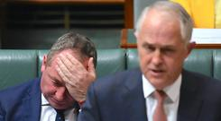 Barnaby Joyce reacts behind Australian Prime Minister Malcolm Turnbull in the House of Representatives