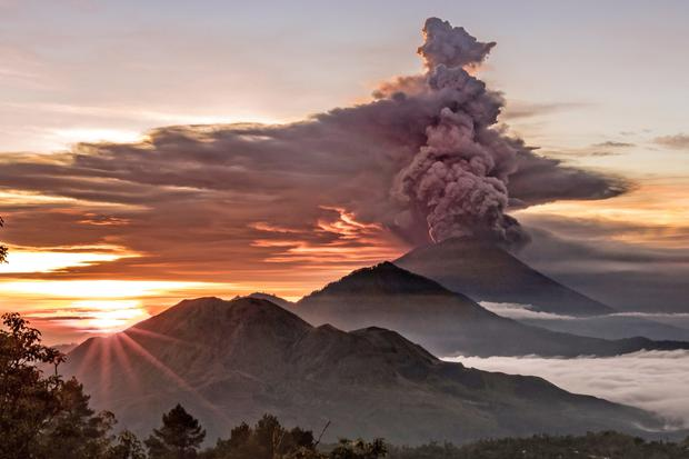 Mount Agung volcano spews smoke and ash in Bali yesterday, forcing scores of flights to be cancelled. Photo: Emilio Kuzma-Floyd/Reuters