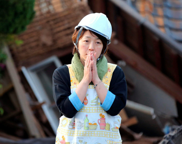 A woman in front of damaged house in Mashiki, Japan after an earthquake in 2016