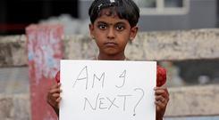 A young child holds a placard during a protest against the rape of an eight-year-old girl in Kathua, near Jammu, in Kochi, south-western India. Photo: Reuters