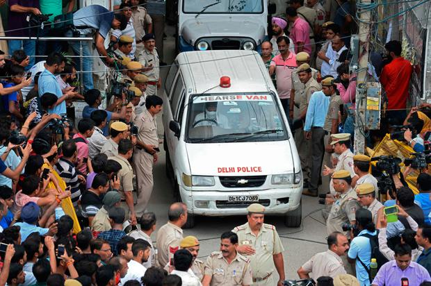 Locals watch as an ambulance takes away one of the bodies. Photo: Getty Images