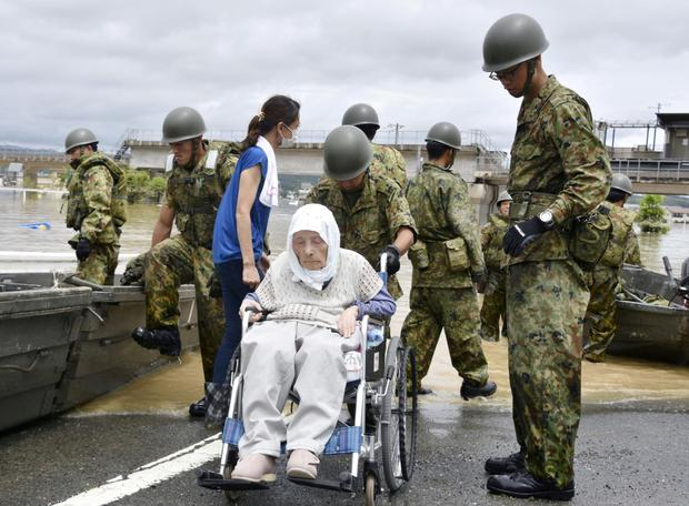An elderly man in a wheelchair is rescued by soldiers. Photo: Reuters