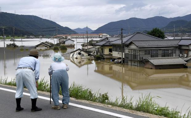 An elderly couple look at a flooded area after heavy rain. Photo: Reuters