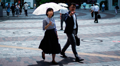 Commuters shield themselves from the sun in Tokyo. Photo: Getty Images