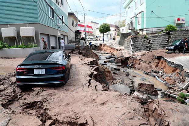 Disaster: A car stuck on a road damaged by the earthquake in Sapporo, Hokkaido, yesterday. Photo: Getty