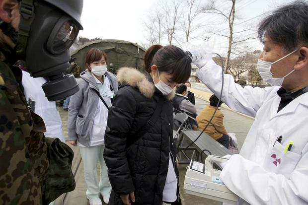 Warning signs: A hospital worker from Fukushima is checked for radioactivity shortly after the power plant was wrecked by the 2011 earthquake and tsunami