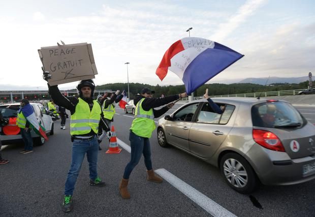 Chaos: Protesters with a sign reading 'Free toll' after they opened toll gates in Antibes, France. Photo: Claude Paris/AP