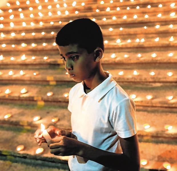 Memorial: A boy holds a candle during a vigil in Colombo in memory of the victims of the Easter attacks. Photo: Thomas Peter/Reuters