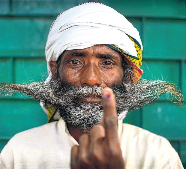 Democracy: An Indian man displays an indelible ink mark on his index finger to show he has cast his vote in the final phase of national elections on the outskirts of Varanasi in the north of the country. Photo: AP