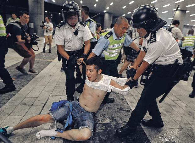 Dragged away: Hong Kong police officers grab a protester during the rally. Photo: AP