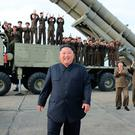 Applause: North Korean dictator Kim Jong-un smiles in front of a launcher used to test-fire a missile at an undisclosed location in the secretive nation. Photo: AP