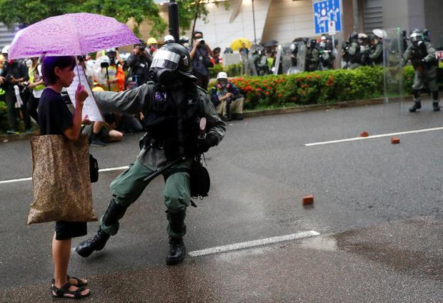 A riot police officer approaches a demonstrator carrying a placard to usher her off the street. Photo: Reuters