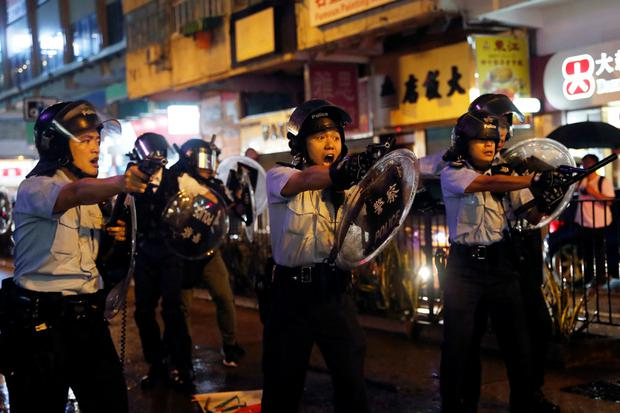Danger: Police officers point their guns at protesters just metres away at Tsuen Wan in Hong Kong. Photo: Tyrone Siu/Reuters