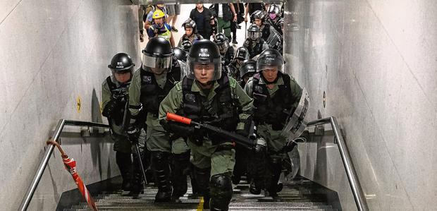 Police officers looking for protesters run out of a metro station