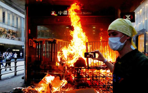 Clashes: A man films a fire set by protesters at the entrance of a subway station in Hong Kong. Photo: Anushree Fadnavis/Reuters