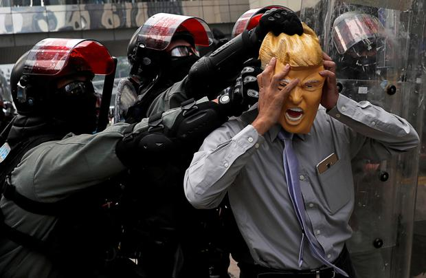 Crowd control: An activist wearing a Donald Trump mask faces riot police during a protest in Hong Kong. Photo: Susana Vera/Reuters