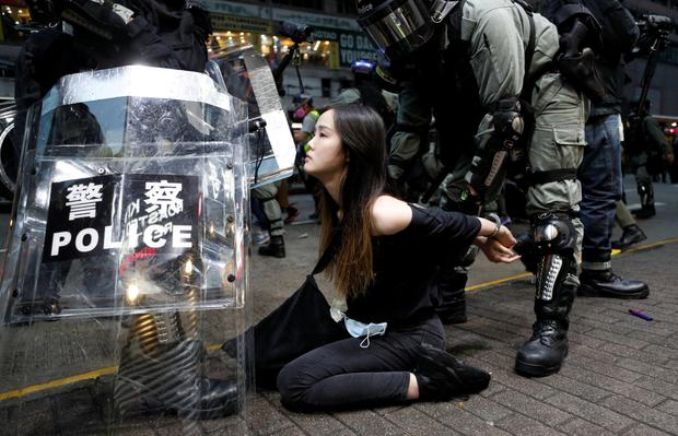 Held: Riot police cuff an activist during a rally in central Hong Kong. Photo: Jorge Silva/Reuters