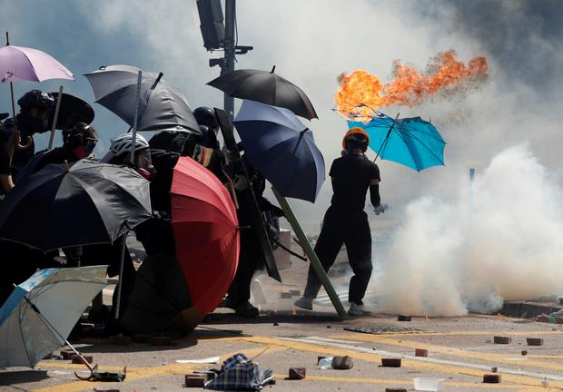Danger: A protester's umbrella catches fire as Molotov cocktails are thrown during clashes with police outside Hong Kong Polytechnic University. Photo: Adnan Abidi/Reuters
