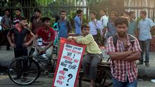 A Bangladeshi boy holds a placard and sits on a cart during a protest against the killing of blogger and author Ananta Bijoy Das, in Dhaka, Bangladesh