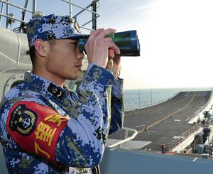 A naval soldier of the Chinese People's Liberation Army looks through binoculars on board China's first aircraft carrier 'Liaoning' as it visits a military harbour on the South China Sea in Hainan province