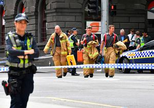 Rescue workers cross a major intersection after a car struck pedestrians in the central business district of Melbourne, Australia, Friday, Jan. 20, 2017. A man deliberately drove into a street crowded with pedestrians on Friday, killing people, police said. Officials said the incident had no links to terrorism. Photo: AP Photo/Andrew Brownbill